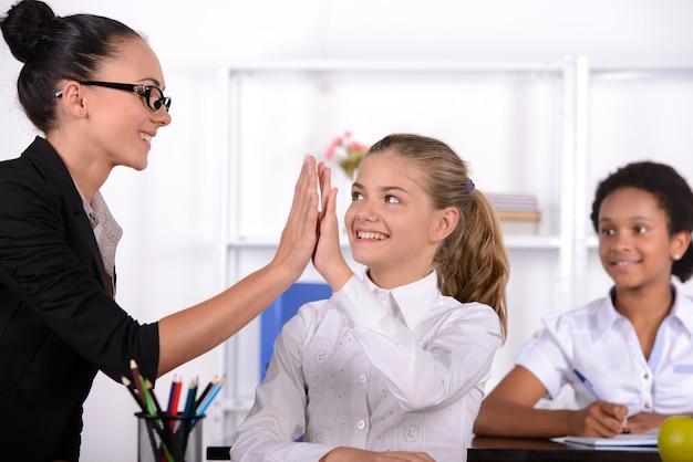 Die lehrerin gibt weiblichen schülern high five.