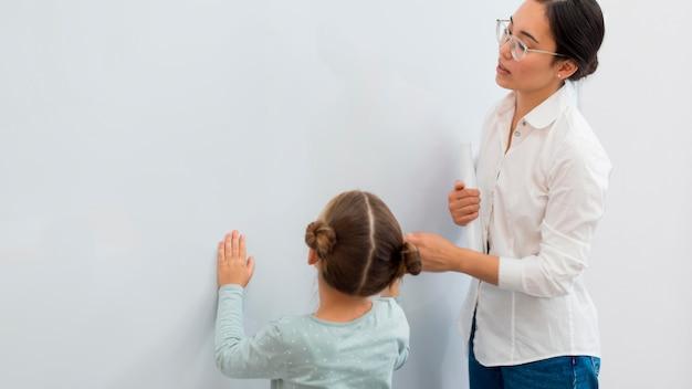 Die lehrerin sagt ihrer schülerin, was sie auf eine weiße tafel schreiben soll