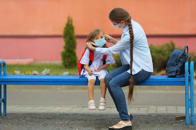 Die lehrerin überprüft und hilft dem mädchen, die maske richtig aufzusetzen, um coronavirus zu verhindern