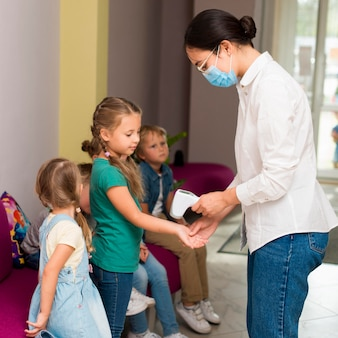 Die lehrerin überprüft während der pandemie die temperatur ihrer schüler für den unterricht