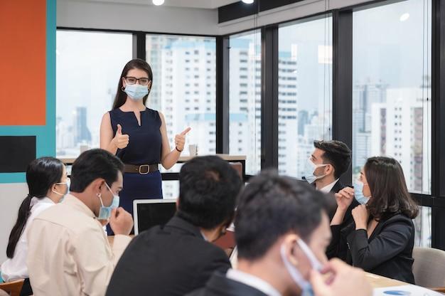 Die leitende frau, die daumen hoch zeigt, schlägt eine unternehmensrichtlinie zum tragen einer gesichtsmaske in der firma während des meetings vor
