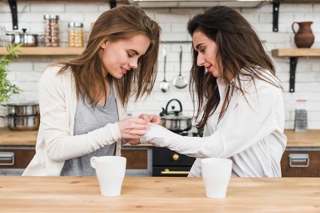 Die lesbische frau, die das hemd ihrer freundin knöpft, legt in der küche beiseite