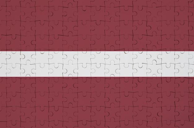 Die lettische flagge ist auf einem gefalteten puzzle abgebildet