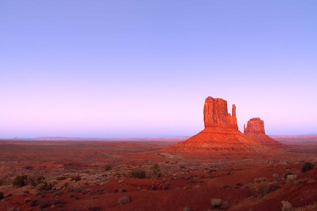 Die letzten strahlen der untergehenden sonne beleuchten die berühmten buttes of monument valley an der grenze zwischen arizona und utah, usa