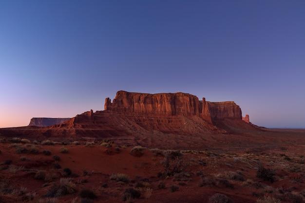 Die letzten strahlen der untergehenden sonne beleuchten die ikonische ansicht des monument valley an der grenze zwischen arizona und utah, usa