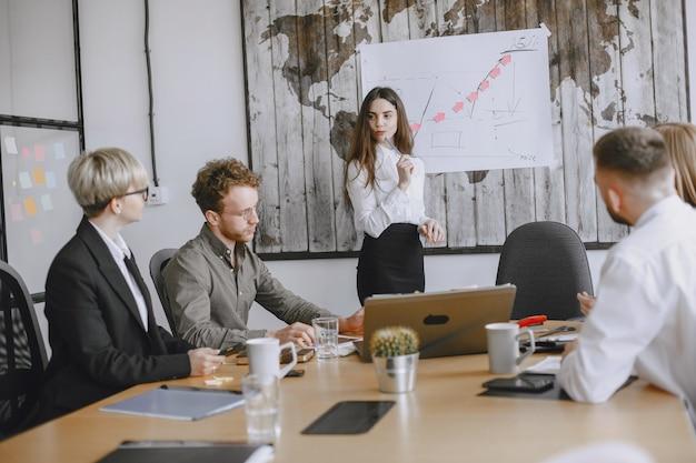 Die leute arbeiten an dem projekt. männer und frauen in anzügen sitzen am tisch. lady zeichnet eine grafik auf den stand.