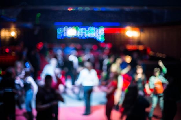 Die leute, die in nachtclub tanzen, verwischten hintergrund. schöne verschwommene lichter auf der tanzfläche