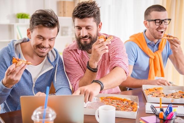 Die leute essen pizza und schauen sich etwas auf dem tablett an.