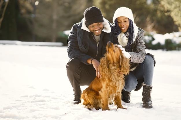 Die leute gehen nach draußen. wintertag. afrikanisches paar mit hund.