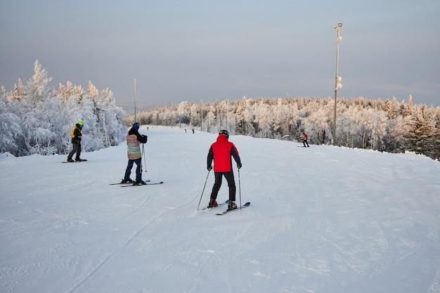 Die leute gehen snowboarden und skifahren, wintererholung und sport. skifahren auf einem snowboard den berg hinunter, lustige gefühle auf den gesichtern von männern und frauen