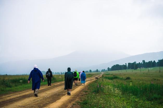 Die leute gehen trotz schlechten wetters in den bergen vorwärts. reisende mit hund gehen die straße hinauf