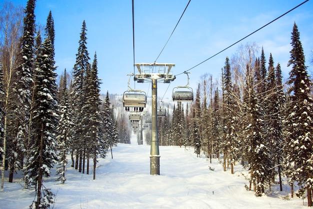 Die leute heben mit dem skilift in den bergen.