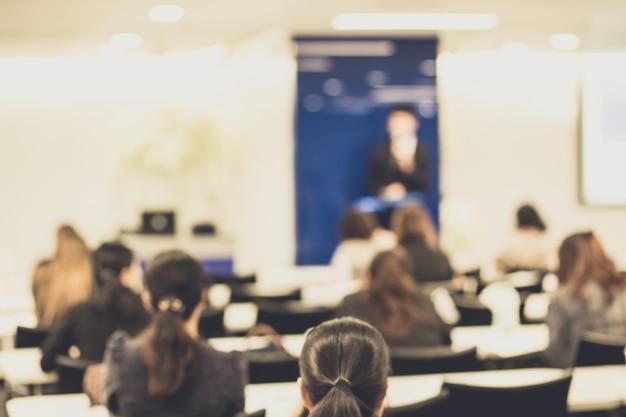 Die leute hören auf einen sprecher, der auf einer firmenkonferenz spricht