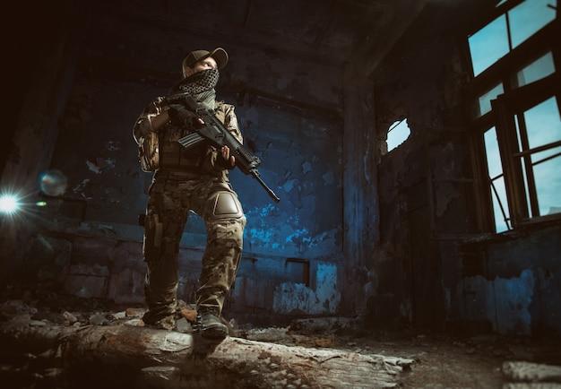 Die leute in uniform mit waffen in den ruinen