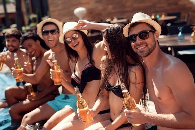 Die leute lächeln und haben spaß im pool.