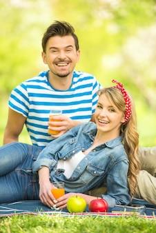 Die leute machen ein picknick im park und trinken saft.