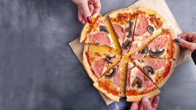 Die leute nehmen ein stück pizza mit pilzen und schinken. draufsicht