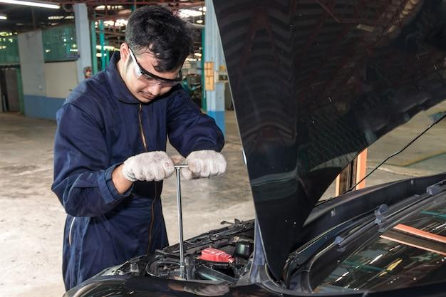 Die leute reparieren ein auto verwenden sie einen schraubenschlüssel und einen schraubendreher, um zu arbeiten.