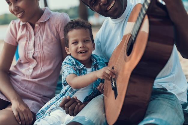 Die leute sitzen mit gitarre auf sandy shore
