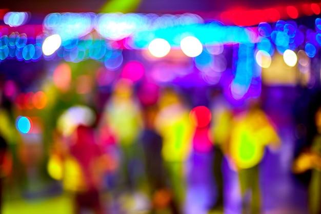 Die leute tanzen, singen, haben spaß und entspannen sich in einem nachtclub mit verschwommenem hintergrund. lichtblitze schöne verschwommene lichter auf der tanzfläche entspannen nachts im club. rauschen, kein fokus
