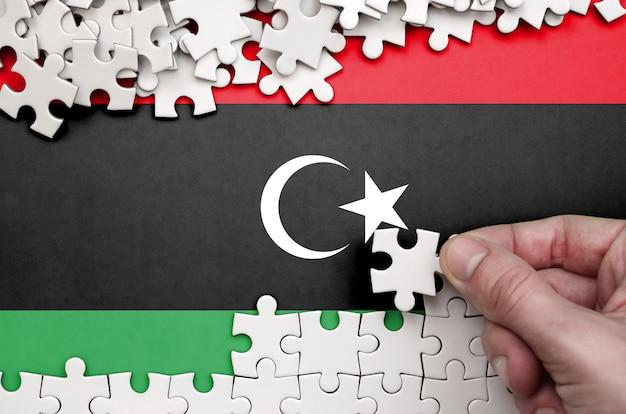 Die libysche flagge ist auf einem tisch abgebildet, auf dem die menschliche hand ein puzzle weißer farbe faltet