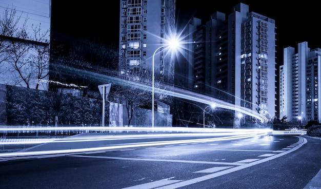 Die lichtspur des hintergrunds der modernen stadtarchitektur mit blauton