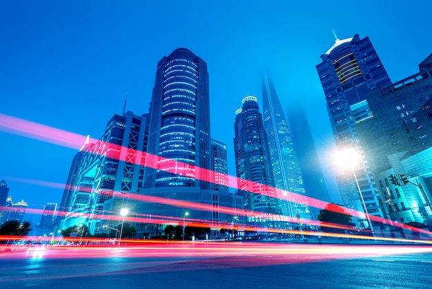 Die lichtspuren auf dem modernen gebäudehintergrund in shanghai china.