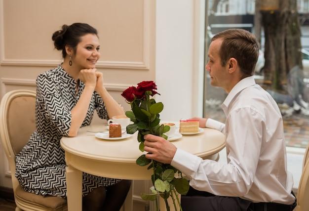 Die liebenden sitzen an einem tisch in einem café mit einem rosenstrauß. konzentrieren sie sich auf einen strauß roter rosen
