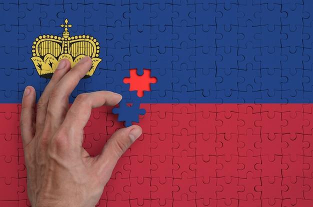 Die liechtensteinische flagge ist auf einem puzzle abgebildet, das der mann mit der hand faltet