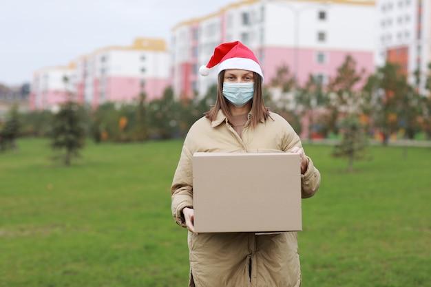 Die lieferfrau in einer roten weihnachtsmannmütze und einer medizinischen schutzmaske hält eine große kiste im freien. lieferung online