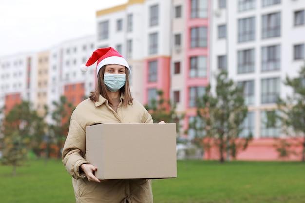 Die lieferfrau in einer roten weihnachtsmannmütze und einer medizinischen schutzmaske hält eine große kiste im freien