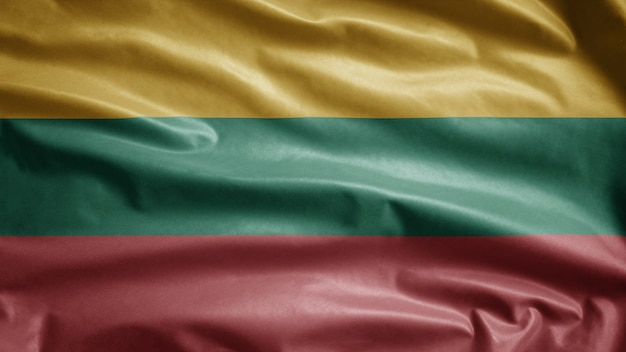 Die litauische flagge weht im wind. nahaufnahme von litauenstate banner weht, weiche und glatte seide. stoff textur fähnrich hintergrund. verwenden sie es für das konzept für nationalfeiertage und länderanlässe.
