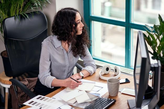 Die lockige brünette designerin sitzt an ihrem arbeitsplatz im büro und schaut durch das fenster. kreatives menschen- und werbegeschäftskonzept.