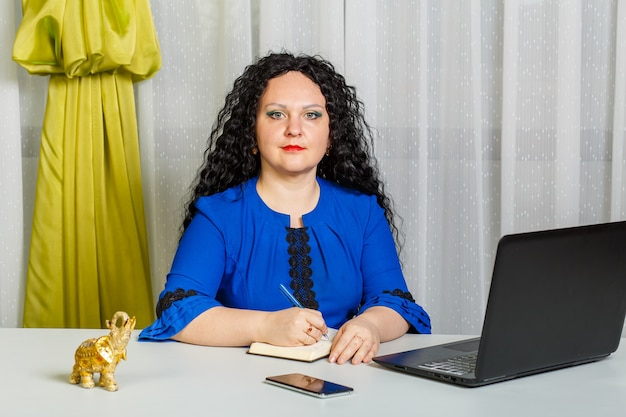 Die lockige brünette frau sitzt an einem tisch im büro hinter einem laptop