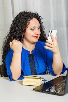 Die lockige brünette frau sitzt an einem tisch im büro und arbeitet mit einem smartphone. vertikales foto