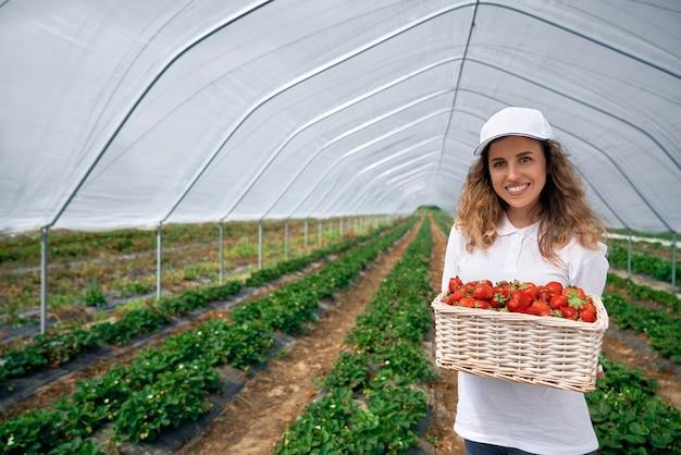 Die lockige brünette hält einen großen korb mit erdbeeren
