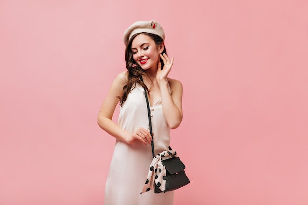 Die lockige dame mit dem roten lippenstift sah schüchtern nach unten. frau im weißen sommerkleid und in der baskenmütze hält schwarze tasche.