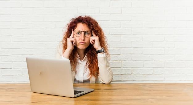 Die lockige frau der jungen rothaarigen, die mit ihrem laptop arbeitet, konzentrierte sich auf eine aufgabe und hielt die zeigefinger, die kopf zeigen.