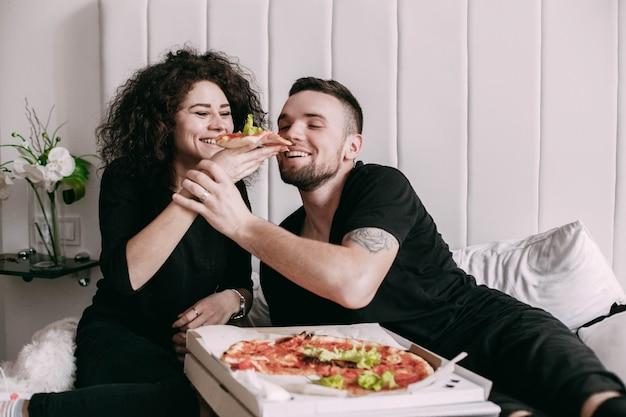 Die lockige frau gibt ihrem mann ein stück pizza