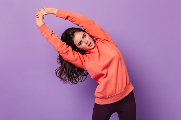 Die lockige frau im sweatshirt schaut nach vorne und macht sportübungen