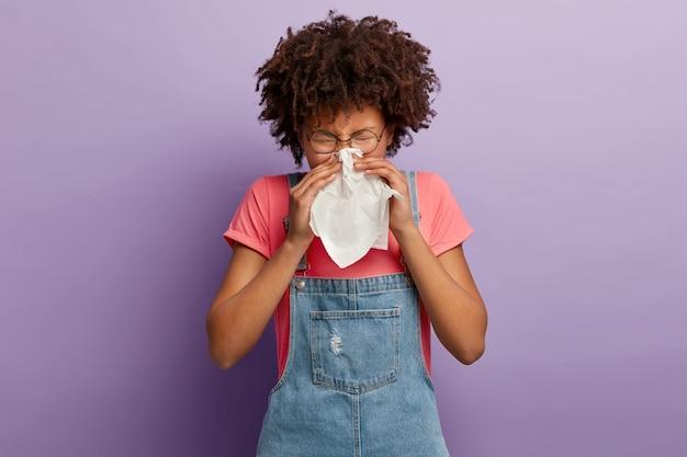 Die lockige junge frau fühlt sich unwohl, putzt sich die nase in weißes gewebe, leidet an laufender nase, erkältungssymptomen oder allergien
