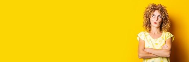 Die lockige junge frau mit verschränkten armen schaut nachdenklich auf gelbem grund nach oben