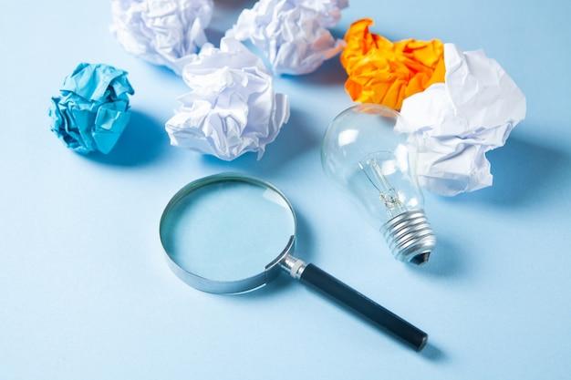 Die lupe betrachtet eine lampe und ein bündel papiere auf einer blauen oberfläche