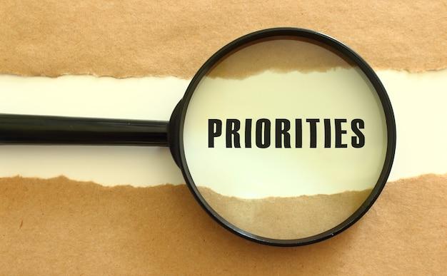 Die lupe zeigt den priorities-text, der hinter dem zerrissenen braunen papier erscheint