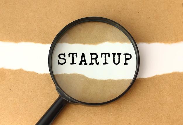 Die lupe zeigt den startup-text, der hinter dem zerrissenen braunen papier erscheint