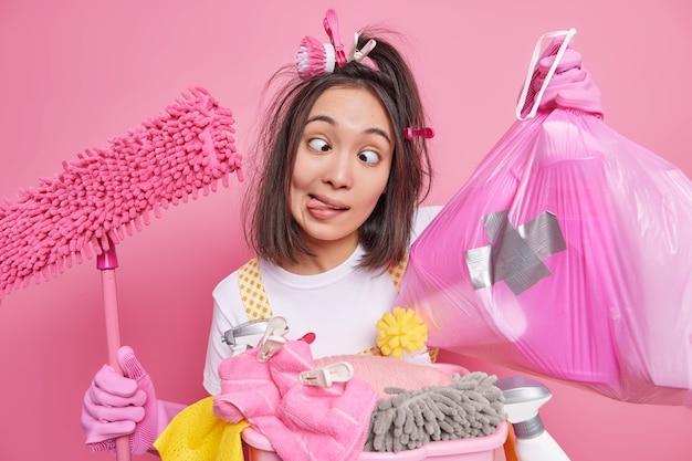 Die lustige asiatische hausfrau albert herum, während sie das haus putzt, macht eine grimasse bei der kamera, kreuzt die augen, streckt die zunge heraus, als ob der narr den müllsack hält und der mopp die wäsche drinnen vor rosafarbenem hintergrund posiert