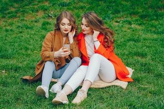 Die Mädchen gehen im Park spazieren.