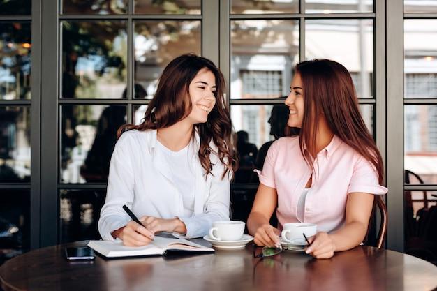 Die mädchen, die im café arbeiten, schreiben wichtige thesen in das notizbuch