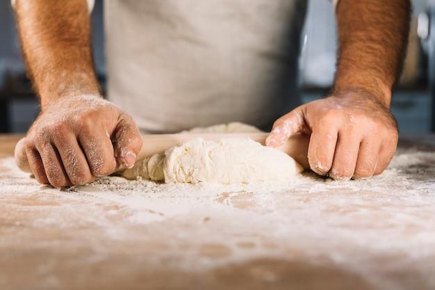 Die männliche bäckerhand, die teig mit nudelholz flach macht