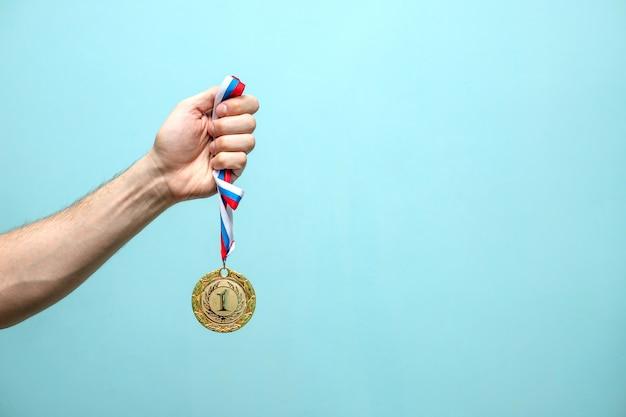 Die männliche hand des siegreichen athleten hält die goldmedaille